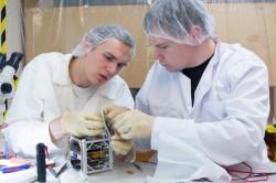 Vasakult TÜ arvutitehnika üliõpilane Erik Ilbis (Tallinna Reaalkoolist), füüsikadoktorant Mihkel Pajusalu (õppinud Treffneris ja Tartu Tamme Gümnaasiumis) monteerivad satelliiti kokku.