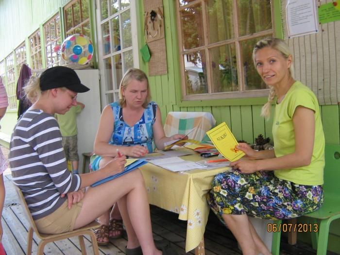 Õpetajad on ametis aukirjade kirjutamisega. Keskel istub Meeli Saarne.