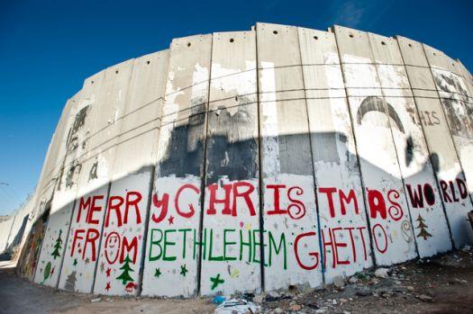 """Juutide ja palestiinlaste konflikt on kestnud piibli aegadest tänaseni ega näi veel nii peagi lõppevat. Saatuse irooniana jääb ka Petlemma linn, kus teatavasti sündis inimkonna suur lepitaja Jeesus Kristus, betoonist turvamüüri varju. Graffititekst: """"Rõõmsaid jõule Petlemma getost!"""""""