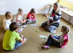 Keeleõpetaja Leelo Kask kutsub lapsed põrandale ringi ja värvikaartide abil uuritakse üheskoos tuttavaid numbreid ja sõnu.