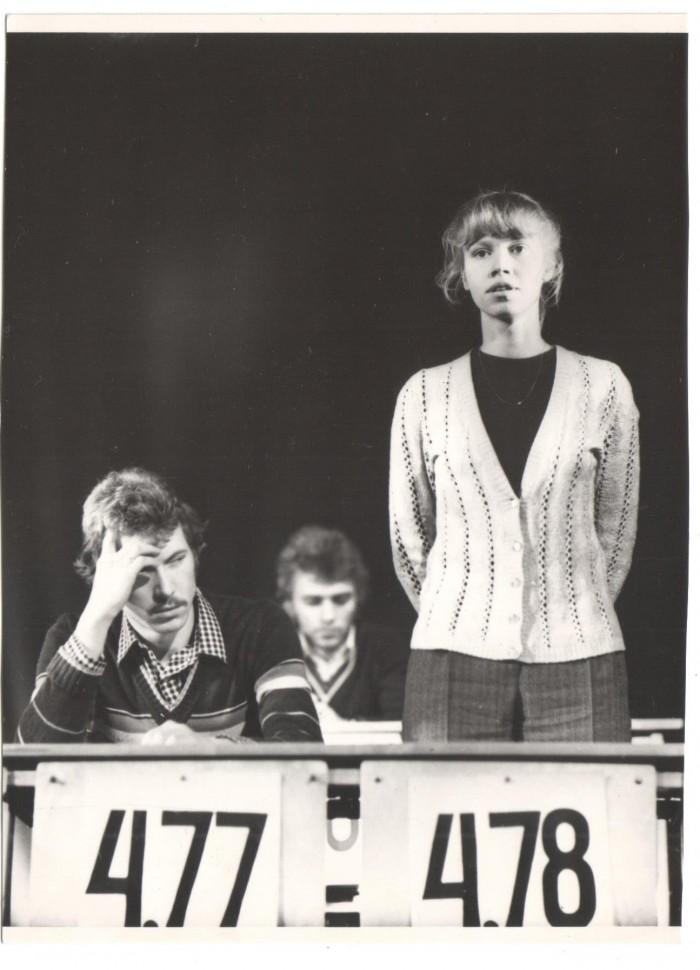 """Katrin Nielsen lavakunstikooli 10. lennu tudengina Merle Karusoo lavastuses """"Meie elulood"""". Noormehed tema kõrval on kursusekaaslased Elmar Trink ja Andres Lepik. Numbrid noorte ees näitavad nende keskkooliaegset keskmist hinnet. Foto: erakogu"""