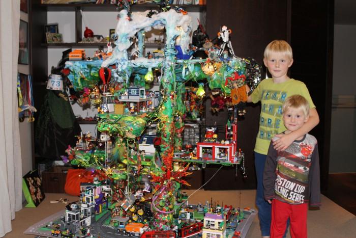 """""""Legopuu"""" HugoBergson (7-aastane). Töö valmis koos emaga. Auhind""""Parimarhitekt"""". Hugo (pildil koos vennaga) hakkas legodest ehitama juba kaheaastaselt. Kui legolinn kattis terve põranda, nii et toas enam liikuma ei mahtunud, valmiski ratastel legopuu. Sinna mahtusid ära kõik olemasolevad ehitised ja ruumi on ka uutele ideedele. Puul on neli korrust. Kõige kõrgemal on Antarktika, kristallikaevandus ja peetakse tähtede sõda. Järgmisel oksal on politseijaoskond, pood, tuletõrjejaam, Simpsonite küla, haldjad ja puuonn. Alumisel korrusel on rongirada, autorada, korterelamud, rand, lõbustuspark ja palju muud. Saarele, kus puu asub, pääseb sadamast laevadega. Korruste vahel liigeldakse helikopterite ja lennukitega, aga on ka liftid, redelid ja allalaskmistrossid. Puul on valgustus, nii et saab ka pimedas mängida."""