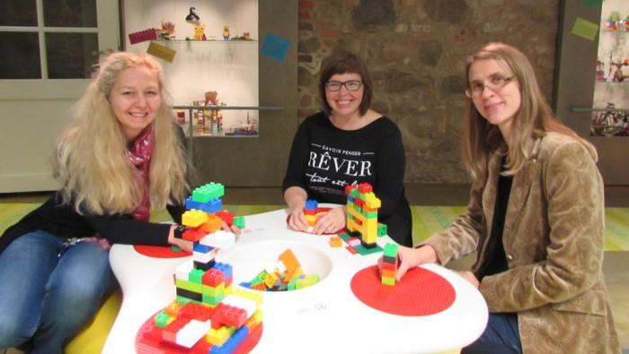 Tartu mänguasjamuuseumi direktor Triin Vaaro, giid-pedagoog AveViirma ning teadur ja peavarahoidja Helena Grauberg proovisid näitusel ka ise legodest meisterdada. Foto: Tiina Vapper