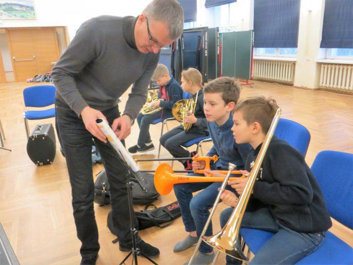 Kolmanda klassi lapsed harjutavad õpetaja Gunnar Pettaigi käe all, põsed punnis, pillimängu, et riigi 100. sünnipäeva aktusel juba ise olla orkestrantide seas. Fotod: Sirje Pärismaa