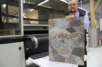 Kompetentsikeskuse juhataja Kalev Kaarna demonstreerib ülikõrge resolutsiooniga pinnaprinteriga valmistatud kivimüüri imitatsiooni. Niisama perfektselt saab selle printeriga jäljendada saare-, tamme-, kase-, vahtra- ja teistegi puuliikide spooni.