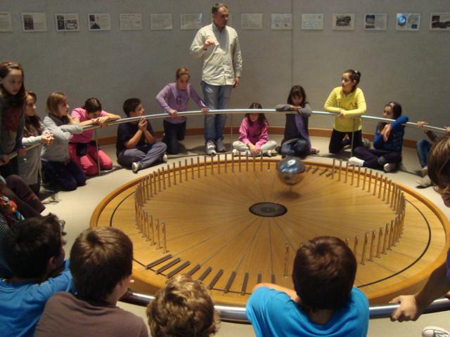 Erakooli füüsikatunnis õpivad lapsed prantsuse füüsiku Jean Bernand Léon Foucault' pendli abil näitlikult, et maakera pöörleb ümber oma telje. Foto: Ellinogermaniki Agogi kool