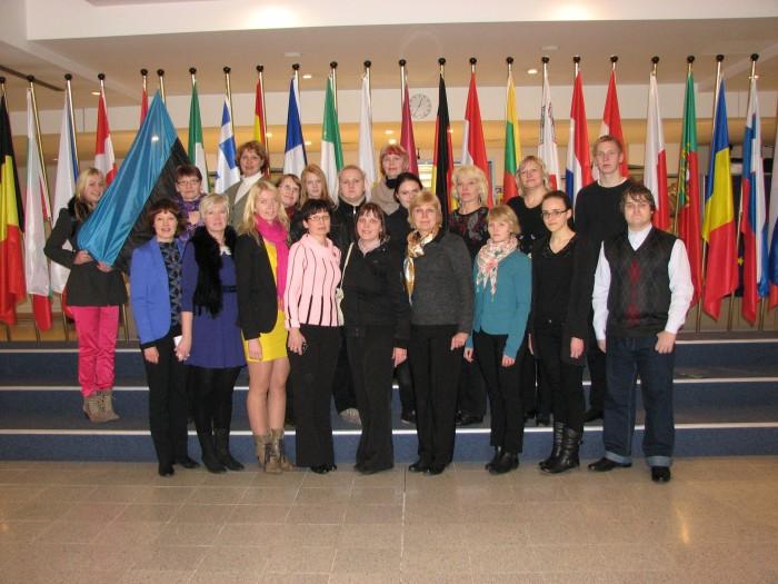 Kanepi Gümnaasiumi õpilased ja õpetajad Euroopa Parlamendis lippude taustal.