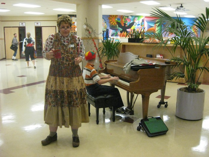 Üks kostümeeritud õpetaja Nohikute päeva hommikul õpilasi fuajees tervitamas. Kooli fuajees oleval klaveril võib mängida igaüks.