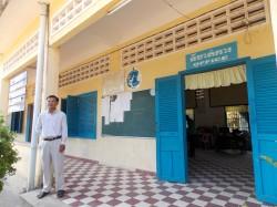 Mey Sovoeun oma algkooli õpetajate toa lävel. Kambodža riigikoolid on oma välisilmelt äravahetamiseni sarnased.